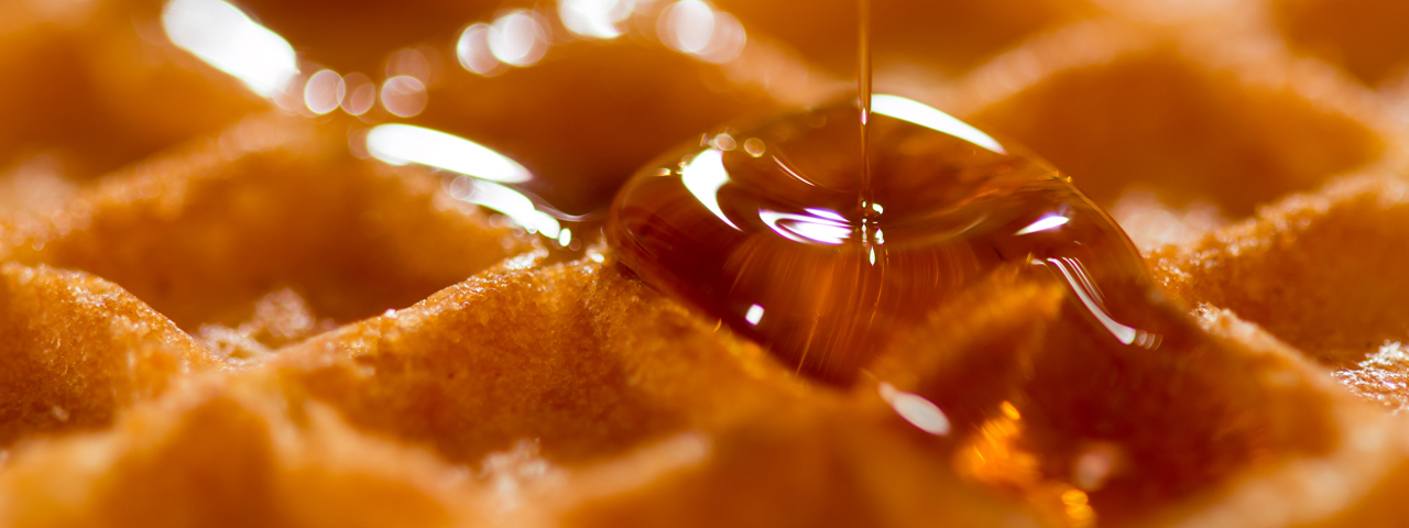Pooring syrup on a Belgian waffle. Together with syrups honey is one of the Food Solutions ingredients we offer in several markets.