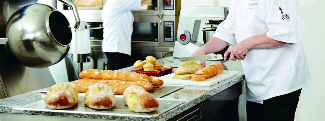 Person cutting bread, we are also active in Food where we offer solutions for Bakeries.