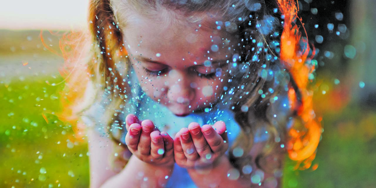 Little girl blowing glittery dust from her hands