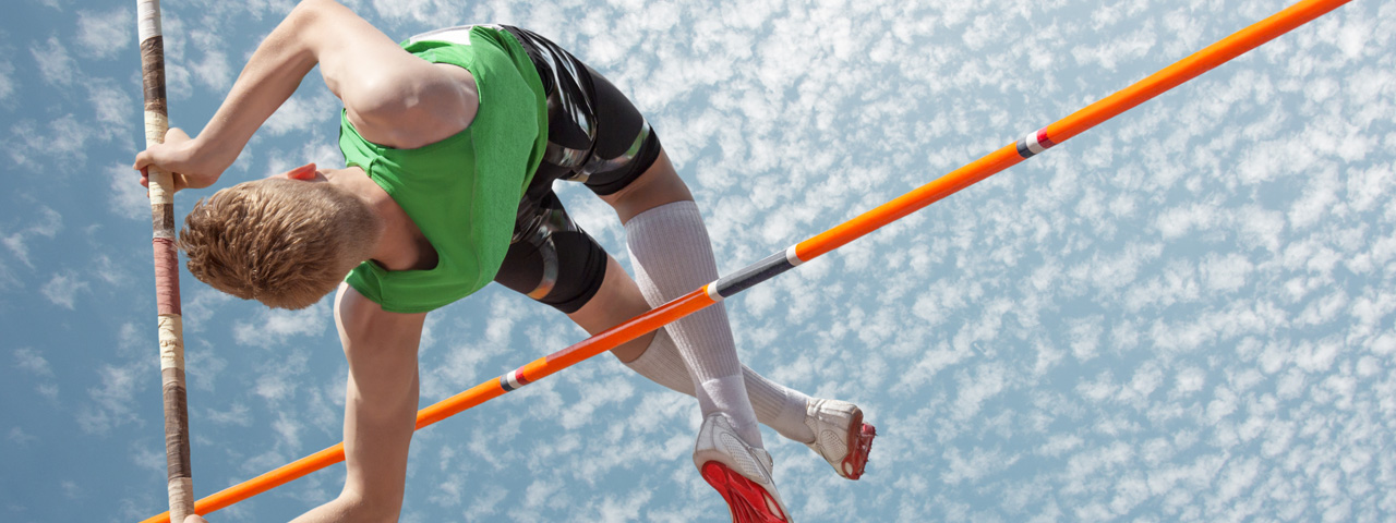 Pole vaulter jumping high against blue sky and white clouds