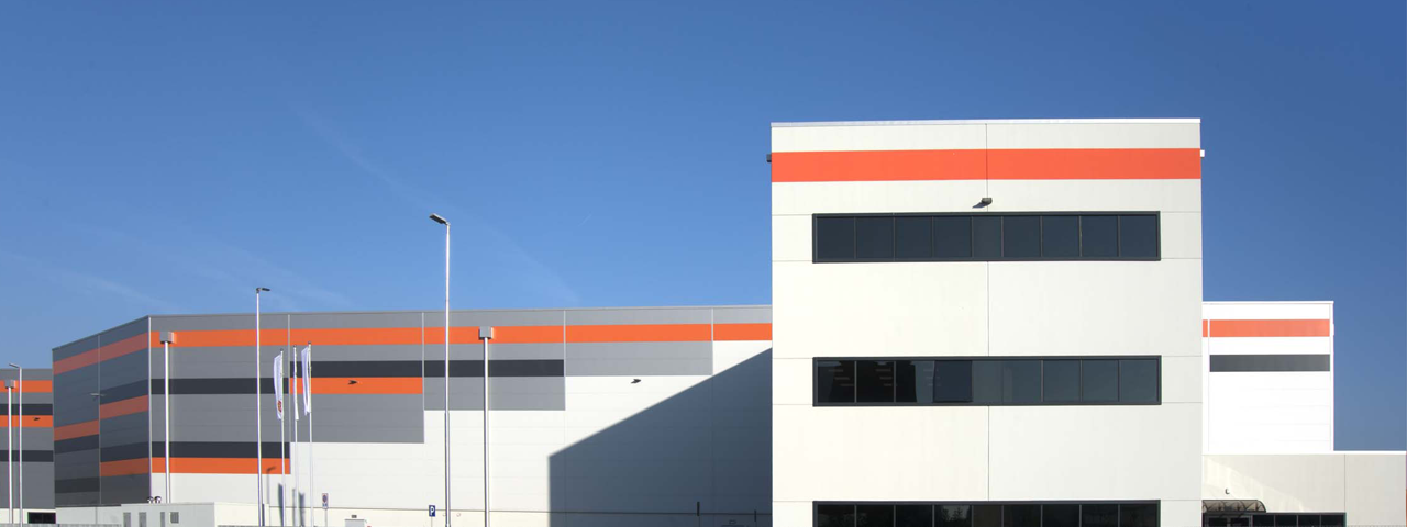 The new Caldic Italia building, a white building with orange, grey and black stripes against a clear blue sky.
