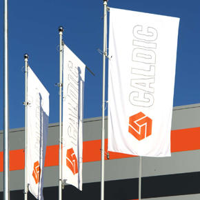 Three white flags with orange Caldic logo in front of the new Caldic Italia location.