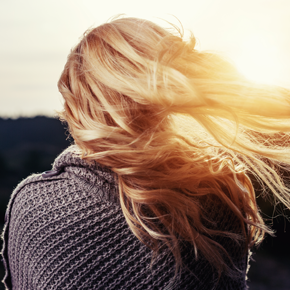 Woman pictured from the back with sun shining through her wavy blond hair