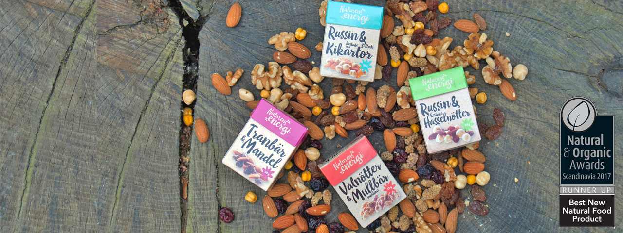 "Our assortment of Naturens energi: small boxes placed on a tree trunk, surrounded by dried fruits and nuts. Awarded Best Natural Food Product ""Runner up"""