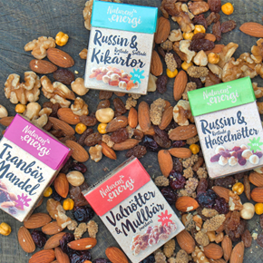 Our assortment of Naturens energi: small boxes placed on a tree trunk, surrounded by dried fruits and nuts