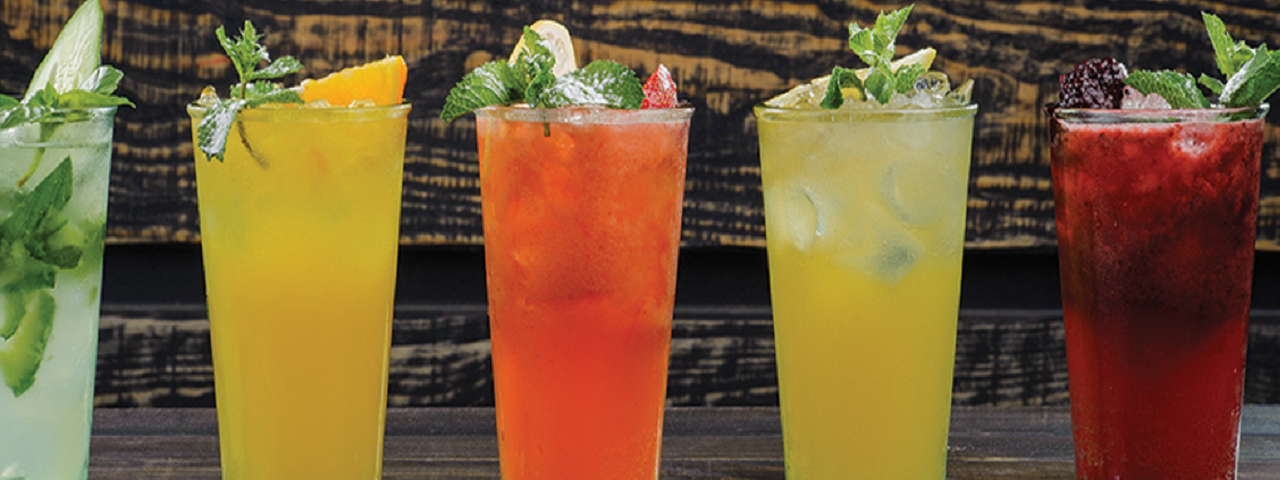 A line up of five refreshing beverages: a cucumber margarita, a citrus margarita, a strawberry margarita, a lemon lime margarita and a blackberry margarita.