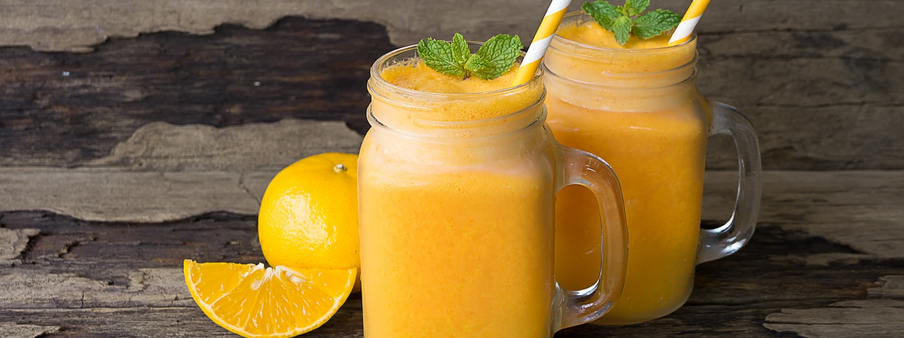 Two mason jars with handles full of an orange coloured protein beverage enhanced with a vitamin and mineral enrichment blend.
