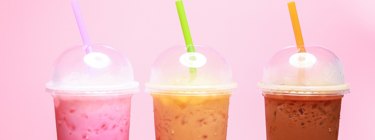 A pink background and three dairy based beverages in plastic take out cups with domed lids.  The pink beverage has a purple straw, the orange beverage has a green straw and the berry beverage has an orange straw.