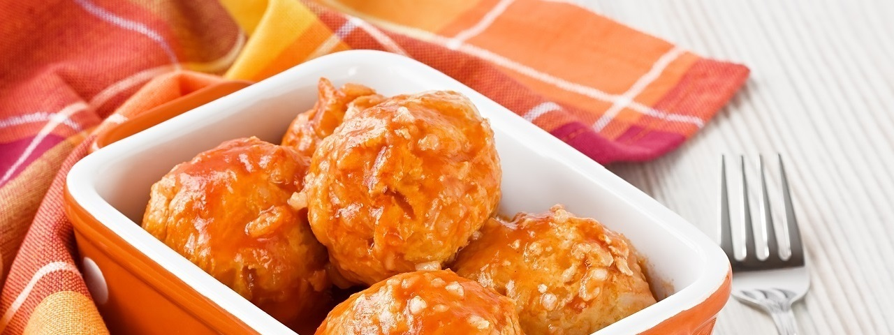 Italian style meatballs in an orange and white ceramic container laying on a multicolored napkin.  There is a stainless steel fork to the right of the container.