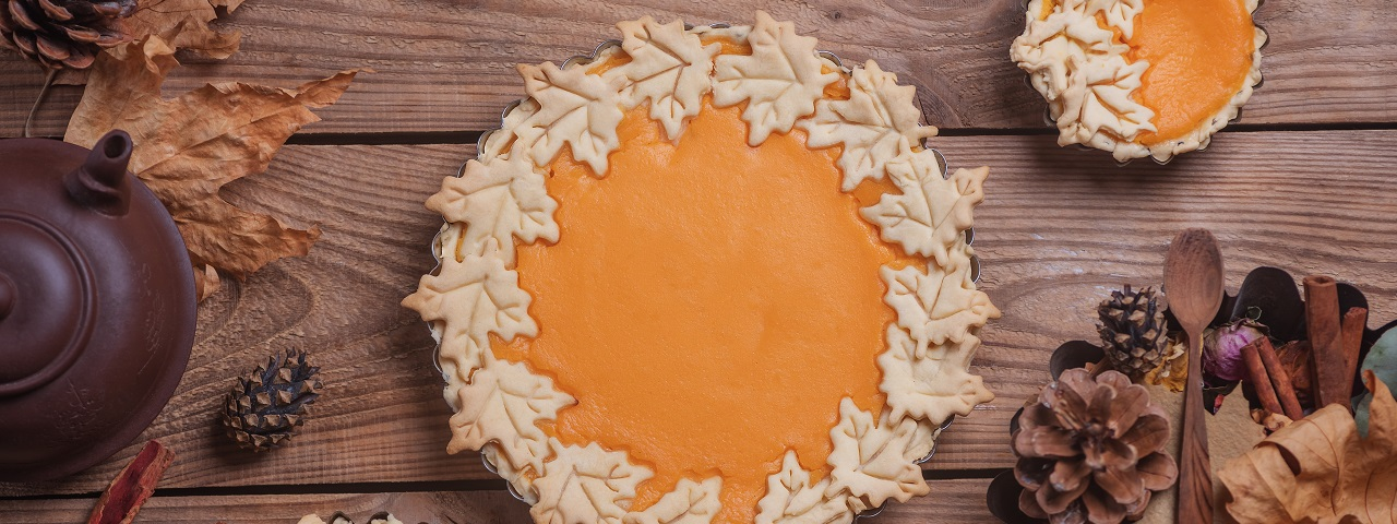 A maple pie embellished with maple leaf shaped crust pieces around the perimeter of the pie.