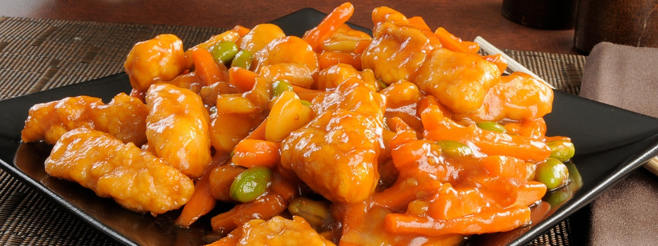 A black lacquered square plate with deep fried chicken pieces, carrots and green onions topped with a sweet and sour glaze.