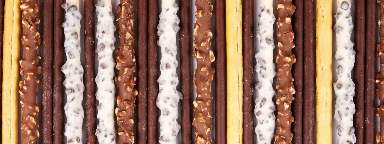 A cross section of cylindricaly shaped cookes coated in different types of chocolate.  From left to right - plain, chocolate covered and dipped in rice crisps, two plain chocolate, white chocolate covered and dipped in rice crisps.