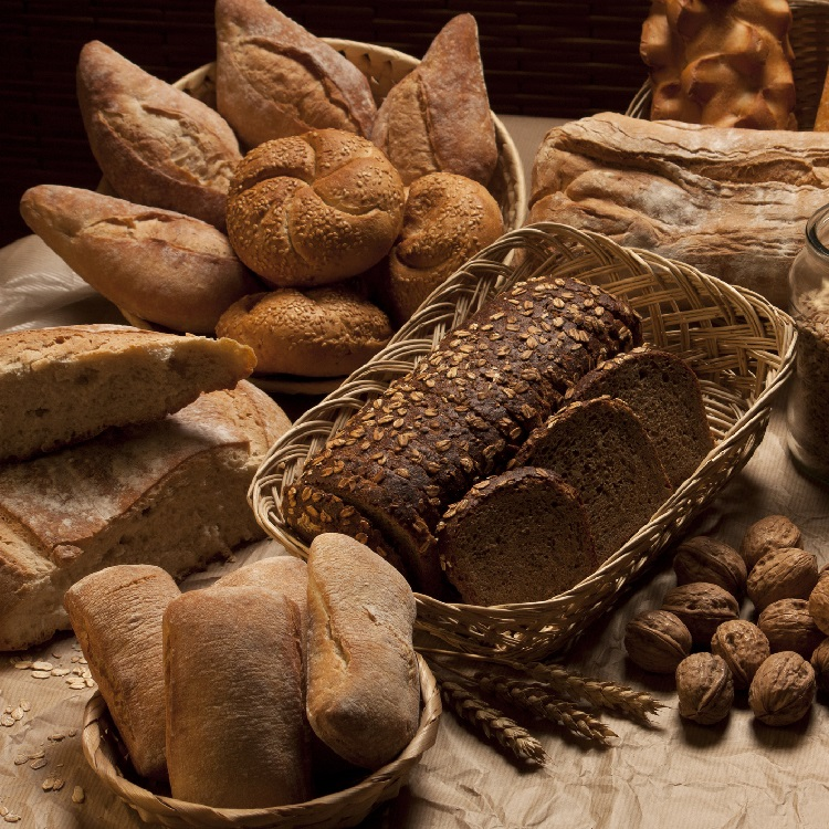An array of artisan baked breads and buns.  There is a basket in the center containing a loaf of sliced dark malt bread.  To the right is a jar of malt grain and a wooden rolling pin.