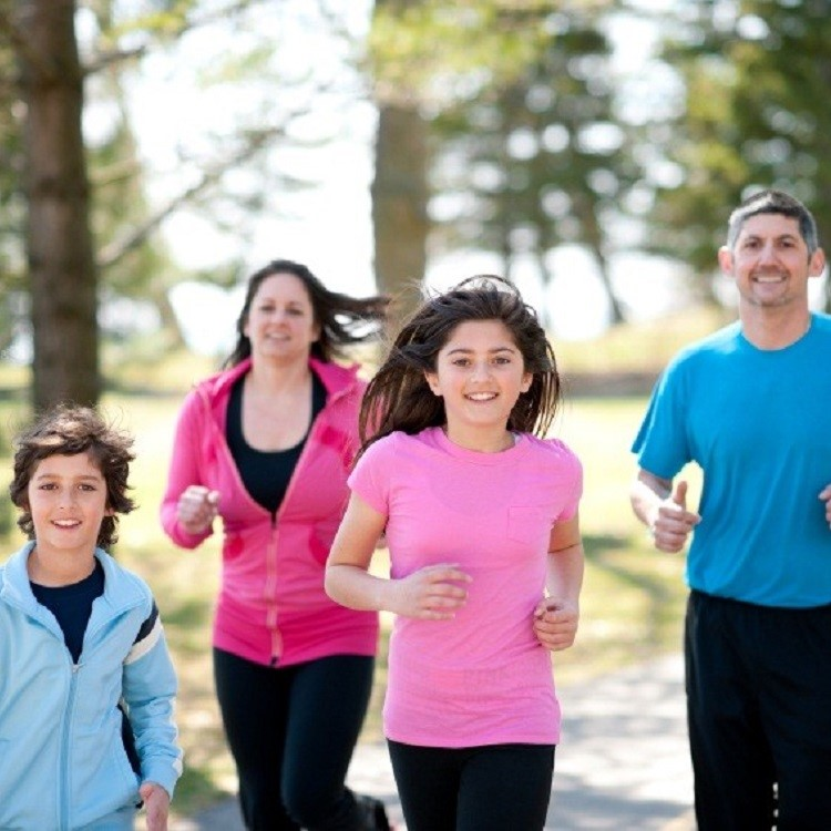 An active family with a young son, adolescent daughter, mother and father jogging together.