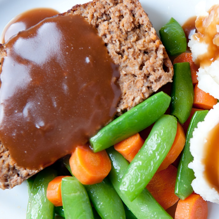 Meatloaf and two scoops of mashed potatoes with a rich, thick gravy with a side of steamed carrots and sugar snap pea pods.