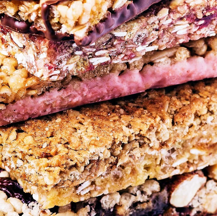 A variety of stacked granola bars with a variety of inclusions including coconut clusters, pralines, oat clusters, and strawberry crunchlets.