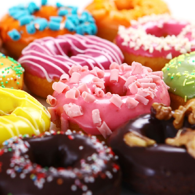 A cross section of a dozen donuts.  There are 5 visible donuts.  Milk chocolate glazed with a darker chocolate drizzle, a lemon yellow glaze with a yellow drizzle, a chocolate covered donut topped with red, blue, green, white and yellow sprinkles, a pink glazed donaut with pink sprinkles and a chocolate glazed donut topped with nuts.