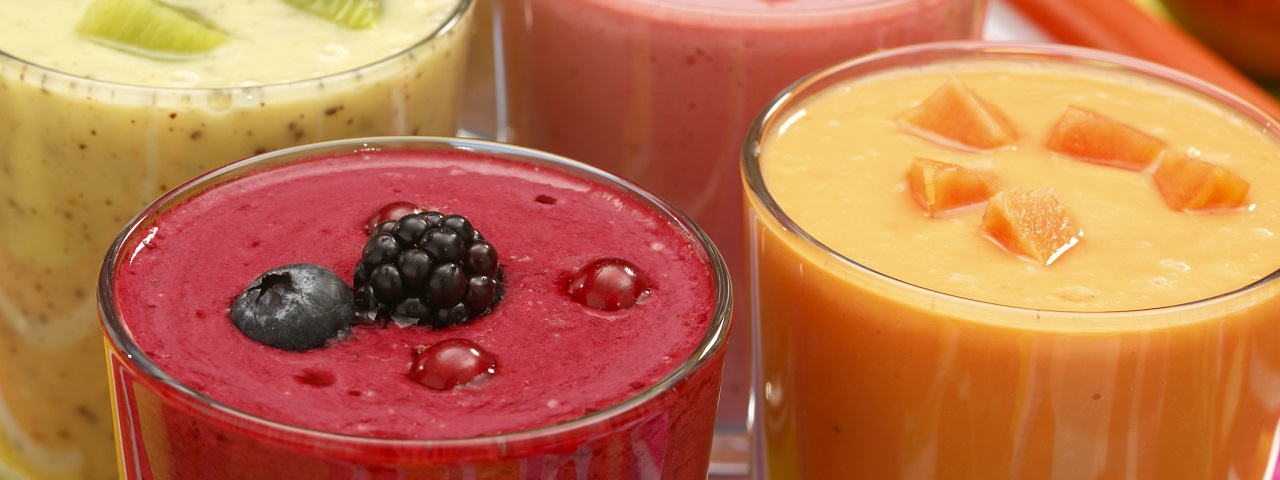 Four glasses containing various smoothies - kiwi, berry, peach and strawberry.