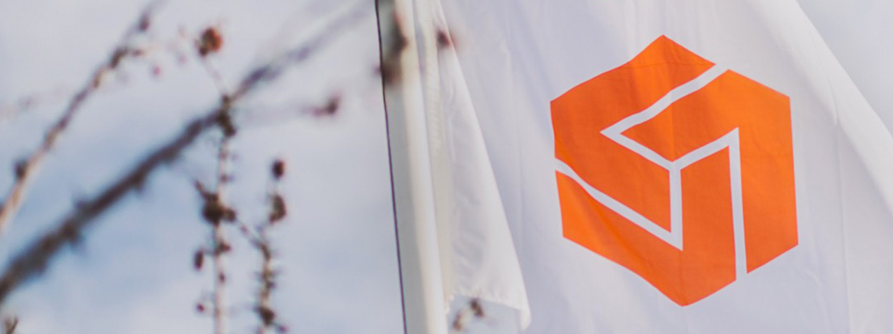 White flag with orange Caldic logo against a cloudy sky and some branches from a tree